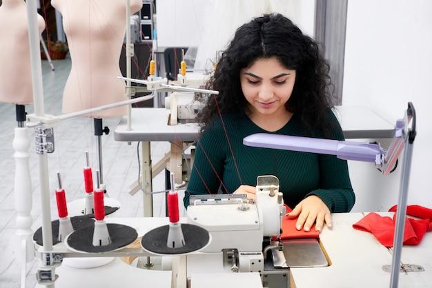 Sarta utilizzando una macchina da cucire overlock professionale nello studio dell'officina