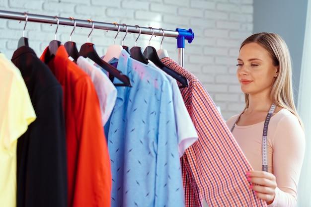 Sarto della donna che controlla i vestiti finiti nel suo ufficio