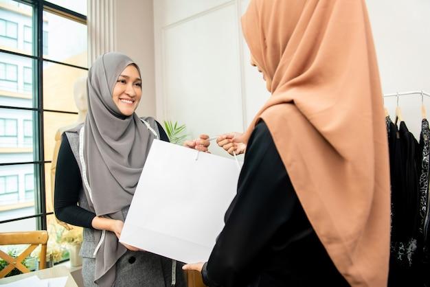Sarto musulmano asiatico dando una borsa al cliente
