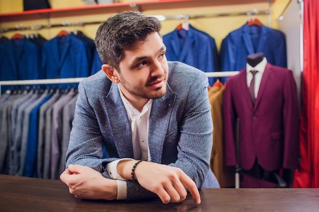 Sarto, sartoria. abito da uomo, sarto nel suo laboratorio. abiti da uomo eleganti appesi in fila. abiti classici da uomo di lusso su rack nell'elegante boutique da uomo. sbadiglia stanco di scegliere