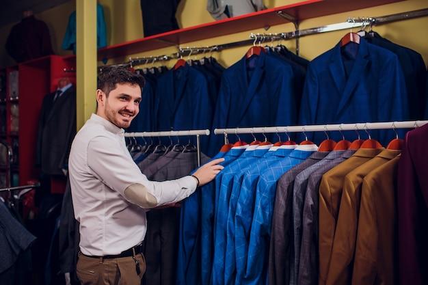 Sarto, sartoria. abito da uomo, sarto nel suo laboratorio. abiti da uomo eleganti appesi in fila. abiti classici da uomo di lusso su rack nell'elegante boutique da uomo.