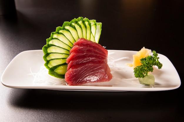 Sashimi con tonno in un piatto bianco. su uno sfondo nero.