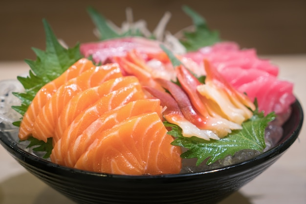 Sashimi di pesce affettato misto su ghiaccio in ciotola nera.