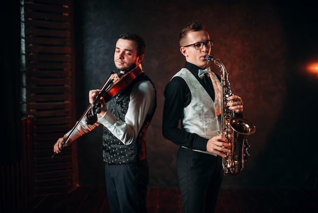Sassofonista e violino suonano melodie classiche