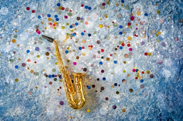Sassofono dorato con paillettes colorate su sfondo blu