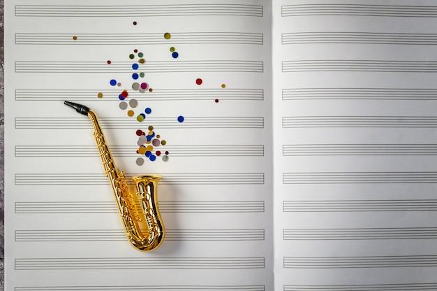 Sassofono dorato con paillettes colorate su sfondo di quaderno di musica