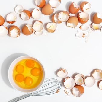 Sbattere le uova con la frusta. tuorli e proteine dell'uovo in una tazza. la corolla sbatte le uova. preparazione di cibo e uova di gallina. guscio d'uovo su un tavolo. vista dall'alto