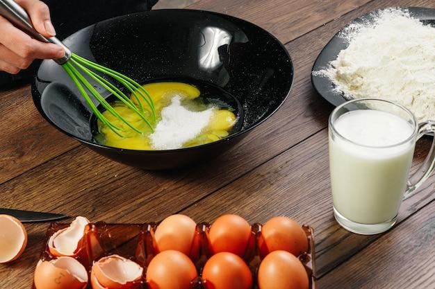 Sbattere le uova. il primo piano delle mani del cuoco unico sbatte le uova
