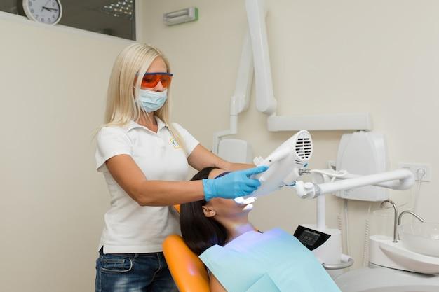 Sbiancamento dei denti con dispositivo di sbiancamento uv dentale, assistente dentale che si prende cura del paziente, occhi protetti con occhiali, trattamento sbiancante con luce, laser, fluoro, sbiancamento artificiale dei denti
