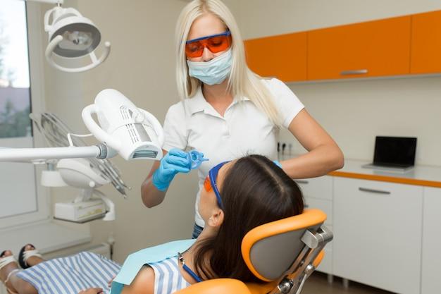 Sbiancamento dei denti con dispositivo sbiancante uv dentale, assistente dentale che si prende cura del paziente, occhi protetti con gli occhiali. trattamento sbiancante con luce, laser, fluoro. sbiancamento artificiale dei denti