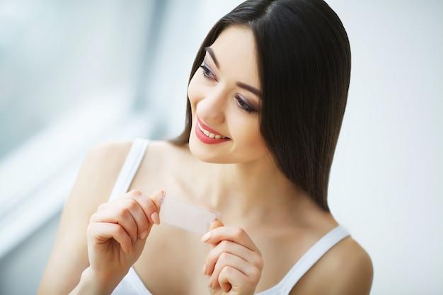 Sbiancamento dei denti. striscia d'imbiancatura della bella tenuta sorridente della donna.