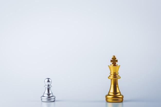 Scacchi del re dorato in piedi nel mezzo degli scacchi d'argento del pegno a bordo.