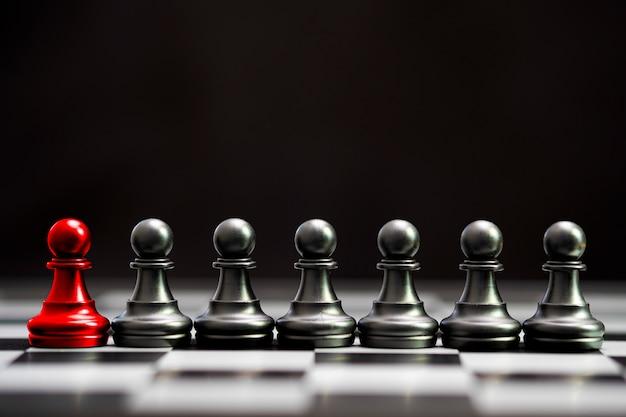 Scacchi di pedone rosso con altri scacchi di pedone neri per leader e pensiero diverso. concetto di disturbo.
