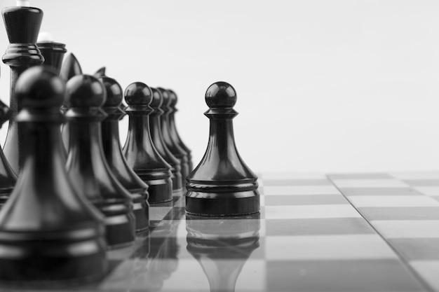 Scacchiera, pezzi neri e prima pedina, gioco di strategia.