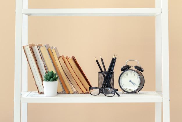Scaffale bianco con libri e articoli di cancelleria contro la parete beige