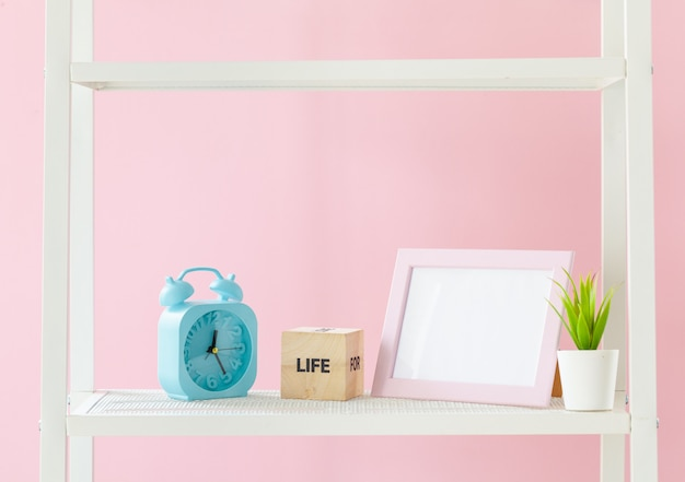 Scaffale bianco con libri e piante contro il muro rosa