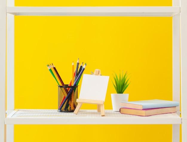 Scaffale bianco con oggetti di cancelleria su sfondo giallo brillante