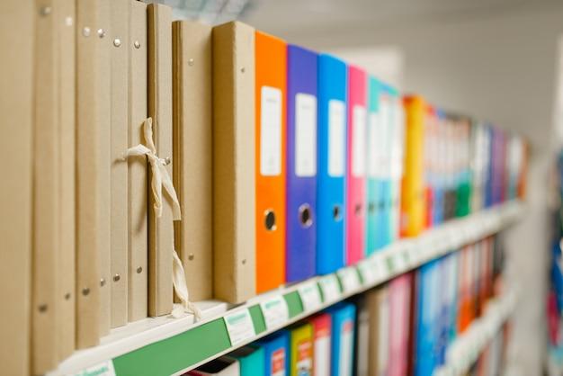 Scaffale con cartelle in cartoleria, nessuno. assortimento di forniture per ufficio in negozio, file di accessori per disegnare e scrivere, materiale scolastico