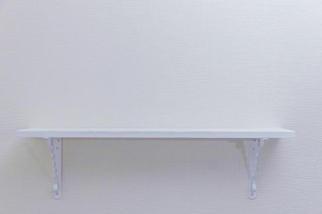 Scaffale di legno bianco vuoto su fondo bianco, copyspace.