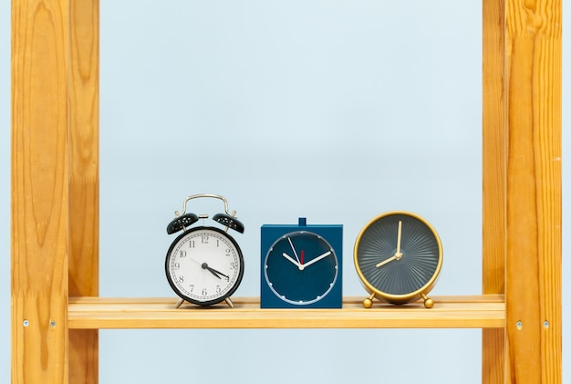 Scaffale di legno con la sveglia e gli oggetti contro fondo blu