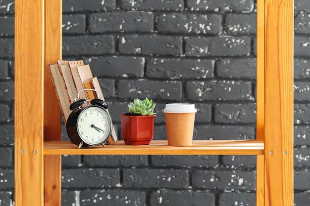 Scaffale in legno con libri e roba contro il muro di mattoni nero
