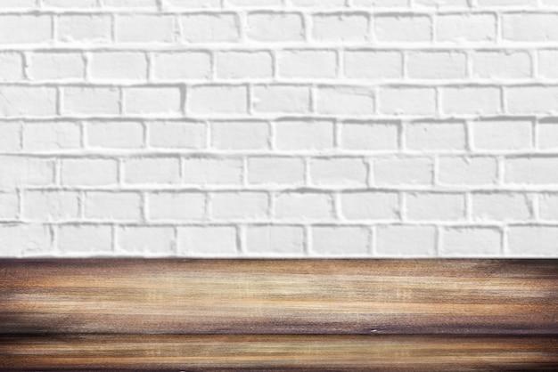 Scaffale o tabella di legno davanti al fondo bianco vuoto vuoto pulito del muro di mattoni con spazio per testo o le idee
