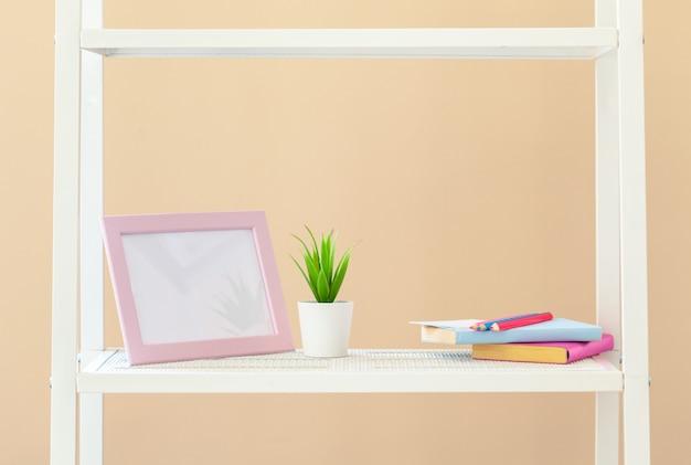 Scaffale per libri bianco con la pianta in vaso contro fondo beige