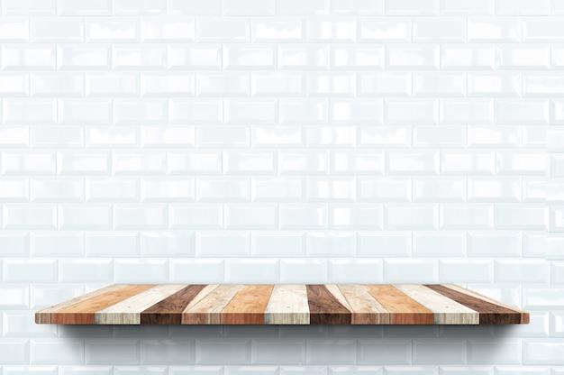 Scaffale per libri di legno vuoto su piastrelle bianche lucide