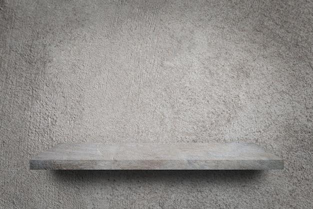 Scaffale vuoto sopra il fondo grigio del muro di cemento