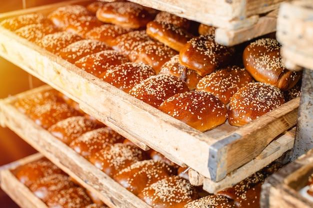 Scaffali di legno con pasticcini freschi in un forno. panini al sesamo.