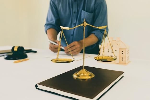 Scala dell'equilibrio d'ottone dell'oro sul libro con il backgroud dell'avvocato