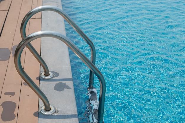 Scala delle scale e gestire la piscina con sfondo blu acqua