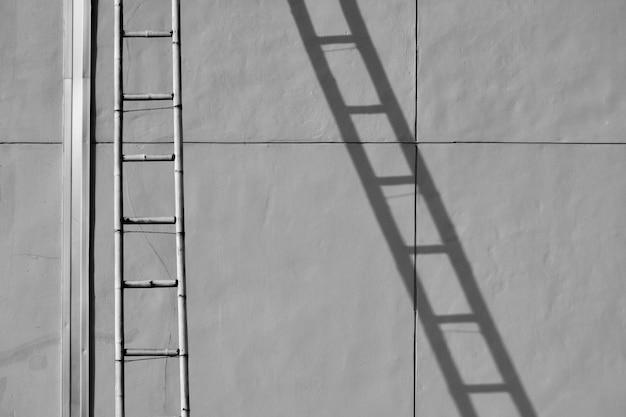 Scala di bambù con ombra sul muro di cemento