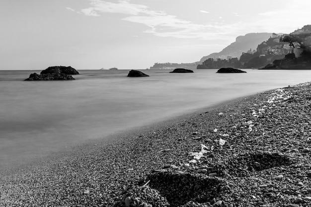Scala di grigi di una spiaggia ricoperta di pietre circondata dal mare con le montagne