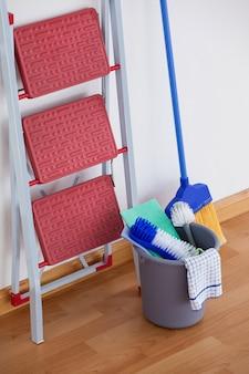 Scala e attrezzature per la pulizia sul pavimento di legno