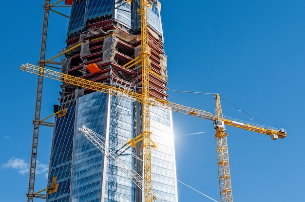 Scala il grattacielo attivo, il bagliore del sole sulle finestre, le gru contro il cielo blu.