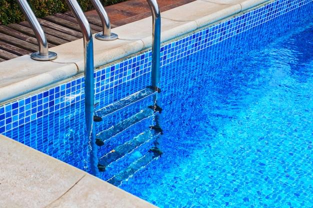 Scala in ferro nella piscina con piastrelle blu