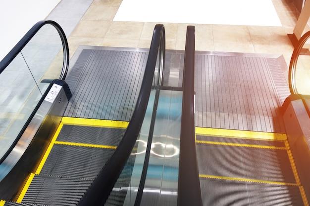 Scala mobile nel centro commerciale del padiglione nella stanza con vetro