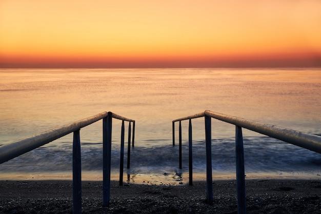Scala per entrare nel mare sulla spiaggia e una bellissima alba in mare