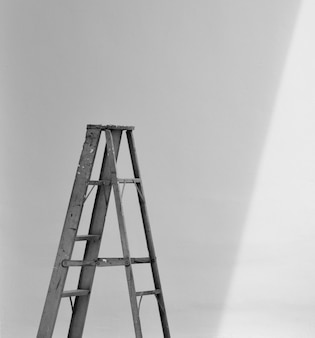 Scala pieghevole in alluminio e l'ombra al muro di cemento bianco