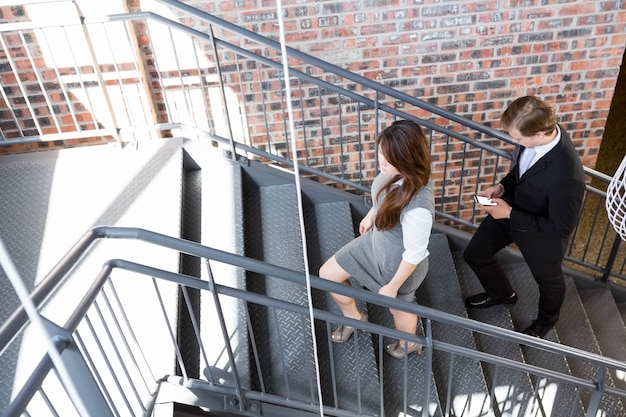 Scala rampicante della donna di affari e dell'uomo d'affari in ufficio