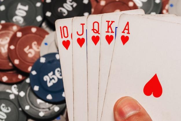 Scala reale nel poker nelle mani del giocatore sullo sfondo di chip di gioco