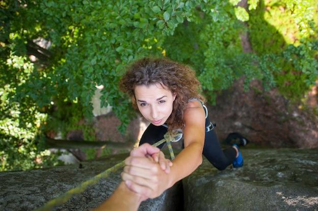 Scalatore che aiuta lo scalatore femminile a raggiungere un picco di montagna