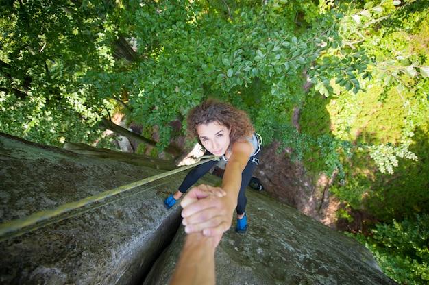 Scalatore che aiuta lo scalatore femminile a raggiungere una cima della montagna