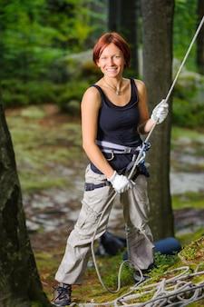 Scalatore della donna che assicura un altro scalatore con la corda