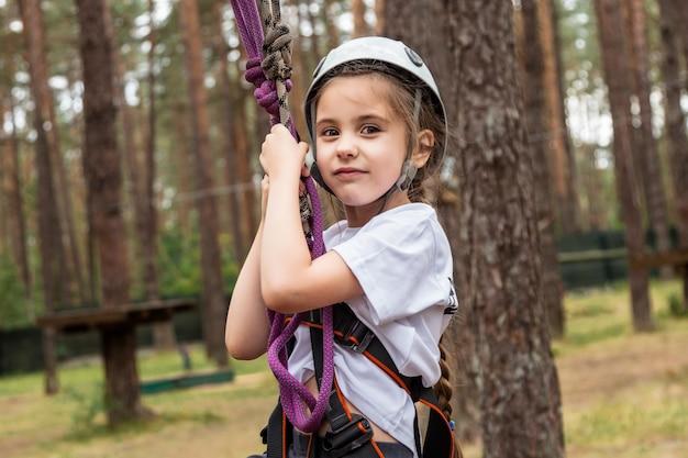 Scalatore della ragazza che appende sull'assicurazione nella foresta