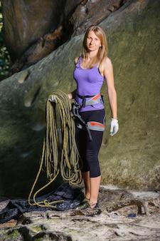 Scalatore femminile che tiene la corda vicino al grande masso
