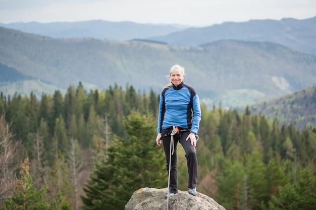 Scalatore femminile sul picco di roccia con attrezzatura da arrampicata