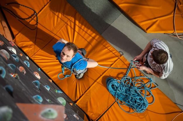 Scalatore maschio che pratica scalando sulla parete della roccia all'interno