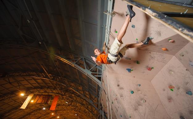 Scalatore maschio che pratica scalare su una parete della roccia all'interno
